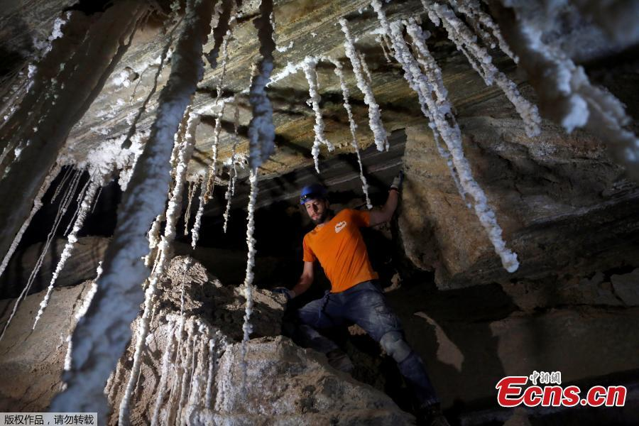 Efraim Cohen, a member of Hebrew University?s Cave Research Center, stands next to salt stalactites inside the Malham Cave, which Israeli researchers say is the world\'s longest salt cave, in Mount Sodom near the Dead Sea, Israel, March 27, 2019. (Photo/Agencies)