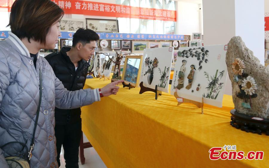 Visitors look at handicrafts made by Wang Zhongxiang using discarded jade fragments in Qilian County, Northwest China\'s Qinghai Province, March 28, 2019. The 55-year-old folk artist is known for his ability to turn the waste into valuable works of art often through time-consuming processes, such as polishing, painting and pasting. (Photo: China News Service/Ma Mingyan)