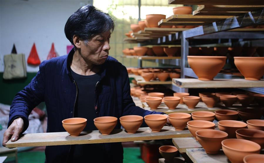 Wu Lizhu, inheritor of the workmanship of Jianzhan teaware, carries pieces of porcelain at his workshop in Jianyang District of Nanping City, south China\'s Fujian Province, March 28, 2019. Jianzhan teaware, a well-known Chinese porcelain originated in Jianyang, dates back to more than 1,000 years ago in Song dynasty (960-1279). It was the best teaware for scholars and literati to use during that time in tea competitions. Jianzhan teawares are known for their variability. Glazes can range in color from dark plum to yellow, green, and blue. During the heating and cooling processes, iron element in the clay can migrate within the glaze to form surface crystals in rich and glossy colors, as in the \