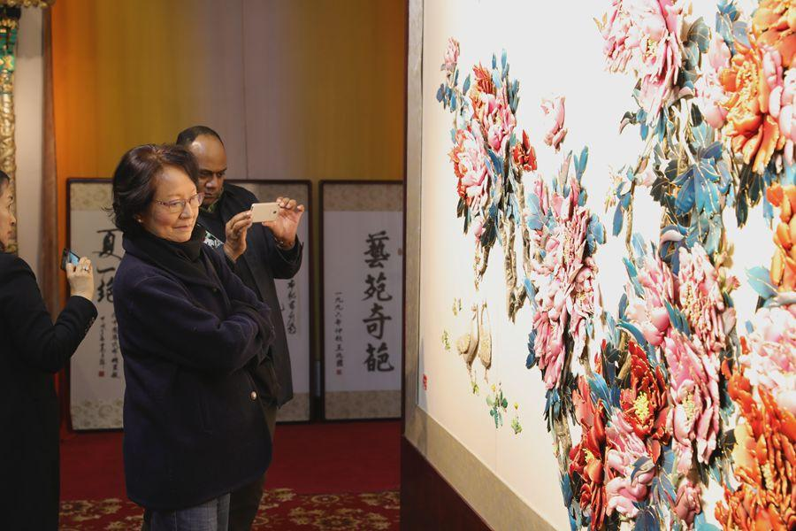Experts from UNESCO are drawn to one of the most famous local works of intangible cultural heritage, a cloth paste painting, on March 27, 2019, in Fengning Manchu autonomous county, Hebei province.(Photo by Fu Rui/chinadaily.com.cn)