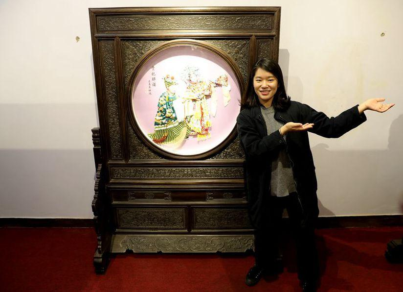 Kim Dongdae, director of the World Heritage Team, poses with a cloth paste painting on March 27, 2019, in Fengning Manchu autonomous county, Hebei province.(Photo by Fu Rui/chinadaily.com.cn)