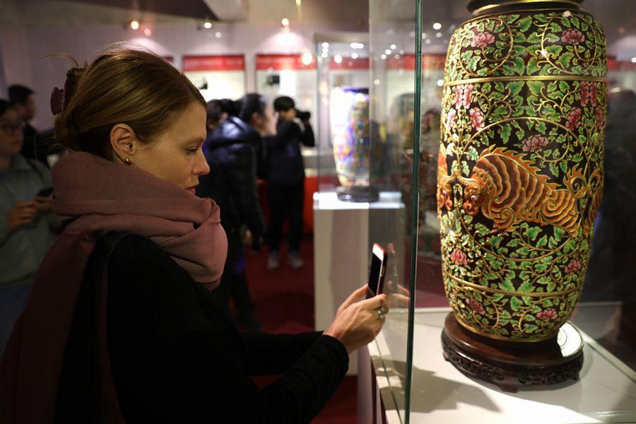 Suzzanne Ogge, UNESCO facilitator for intangible cultural heritage, takes a photo of delicate cloth paste painted patterns on a vase on March 27, 2019, in Fengning Manchu autonomous county, Hebei province.(Photo by Fu Rui/chinadaily.com.cn)