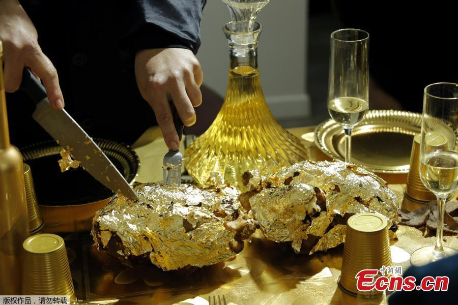 Artist and performer Frederique Lecerf carves a chicken covered with a thin sheet of gold as she prepares her performance meal for guests, a golden dinner with decadent 24 carat gold-covered dishes, in Paris, France, March 28, 2019. (Photo/Agencies)