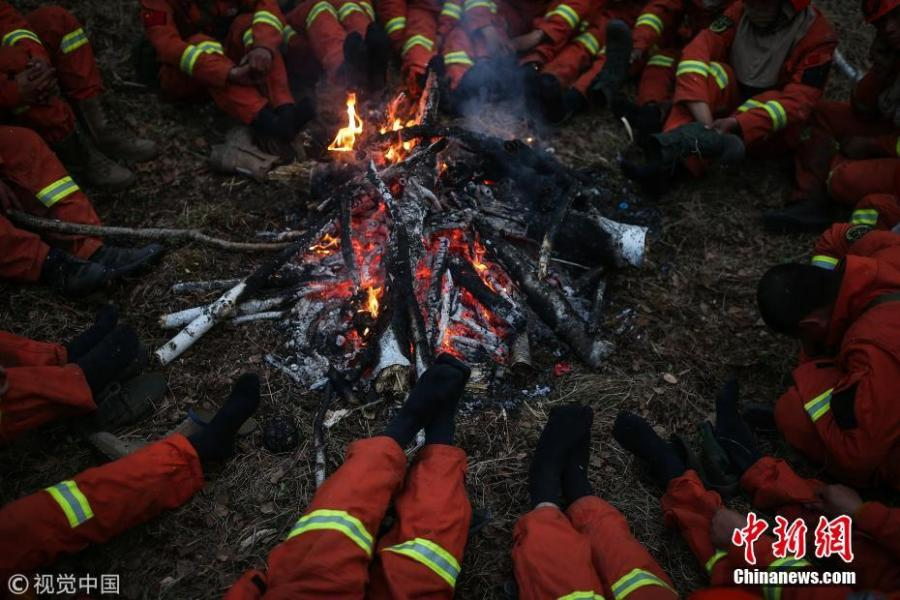 Firefighters took off their cold shoes and warm up in north China\'s Inner Mongolia Autonomous Region on May 20, 2017. (Photo/Agencies)