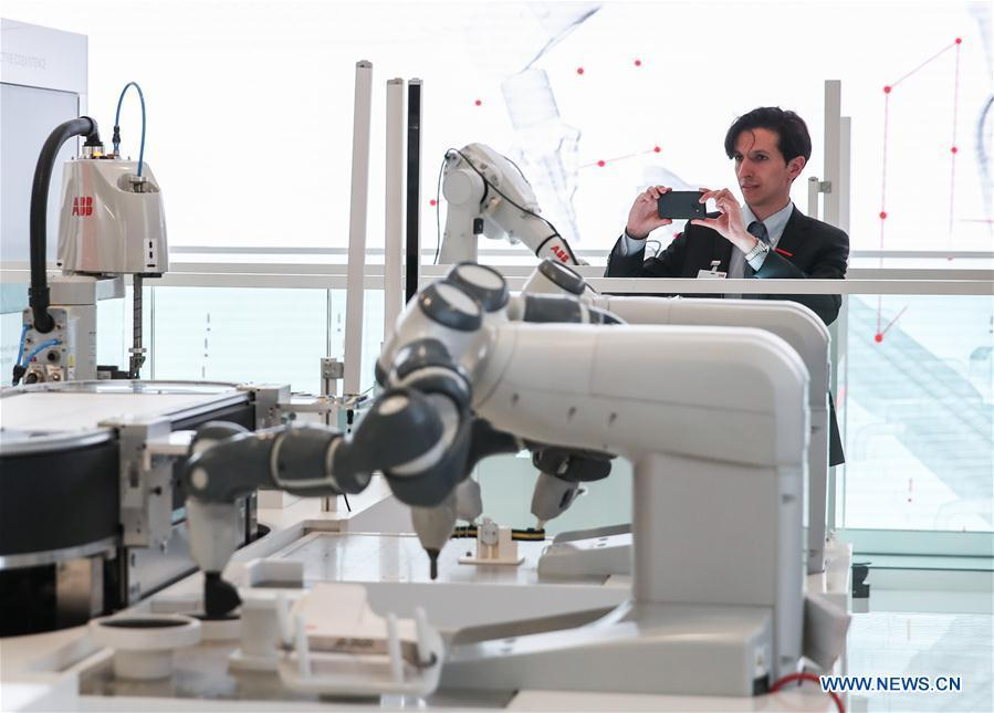 A staff member of the booth of ABB takes photos of displayed robotic arms during the 2019 Hanover Fair in Hanover, Germany, on April 1, 2019. With a total of 6,500 exhibitors from 75 countries and regions, the Hanover Fair shows the latest development of technologies for industrial use, including 5G network, artificial intelligence, light-weight manufacturing, among others. (Xinhua/Shan Yuqi)