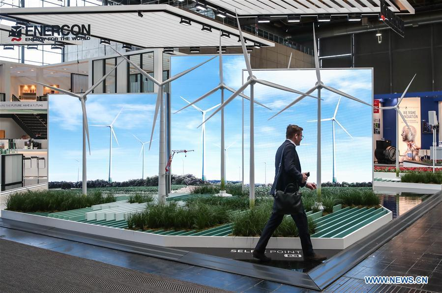 A visitor walks past the booth of Enercon during the 2019 Hanover Fair in Hanover, Germany, on April 1, 2019. With a total of 6,500 exhibitors from 75 countries and regions, the Hanover Fair shows the latest development of technologies for industrial use, including 5G network, artificial intelligence, light-weight manufacturing, among others. (Xinhua/Shan Yuqi)