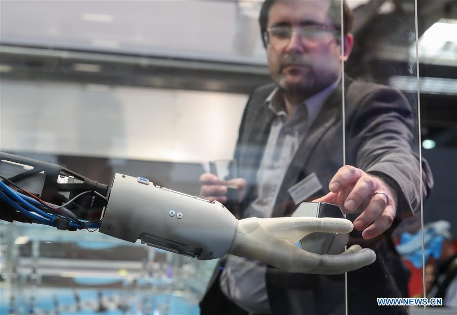 A staff member of the booth of Festo demonstrates a bionic robotic arm during the 2019 Hanover Fair in Hanover, Germany, on April 1, 2019. With a total of 6,500 exhibitors from 75 countries and regions, the Hanover Fair shows the latest development of technologies for industrial use, including 5G network, artificial intelligence, light-weight manufacturing among others. (Xinhua/Shan Yuqi)
