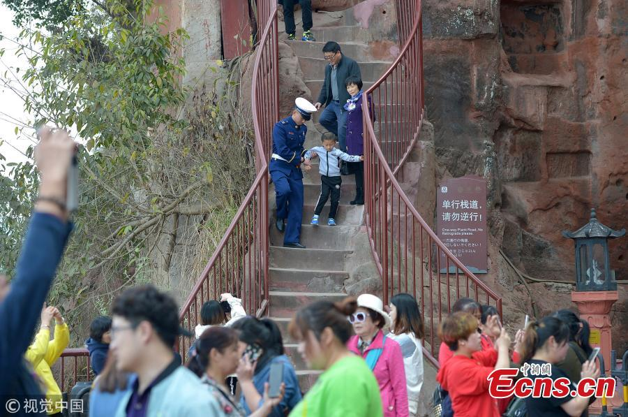 The Jiuqu Zhandao (Nine Bends Plank Road) reopens to tourists at the Leshan Giant Buddha, a UNESCO world heritage site, April 1, 2019. Sixty centimetres at its most narrow and just under one-and-a-half meters at its widest point, the path has 217 steps that wind along a cliff. Standing 71 meters high, the statue was carved out of a hillside in the 8th century and looks down on the confluence of three rivers. (Photo/VCG)