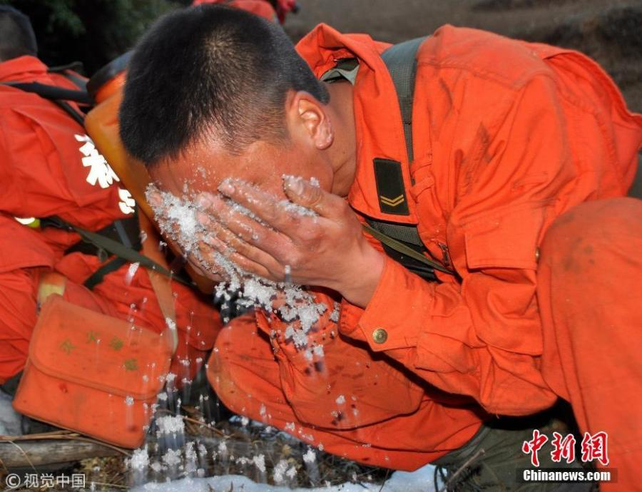 A firefighter puts snow on his face to sooth pain after extinguishing a forest fire, Feb. 6, 2014. (Photo/Agencies)