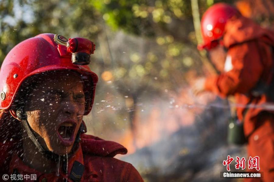 A firefighter suddenly turned back to ask his comrades to spray water on his face to withstand the heat of the fire in southwest China\'s Sichuan Province on March 8, 2015.  (Photo/Agencies)