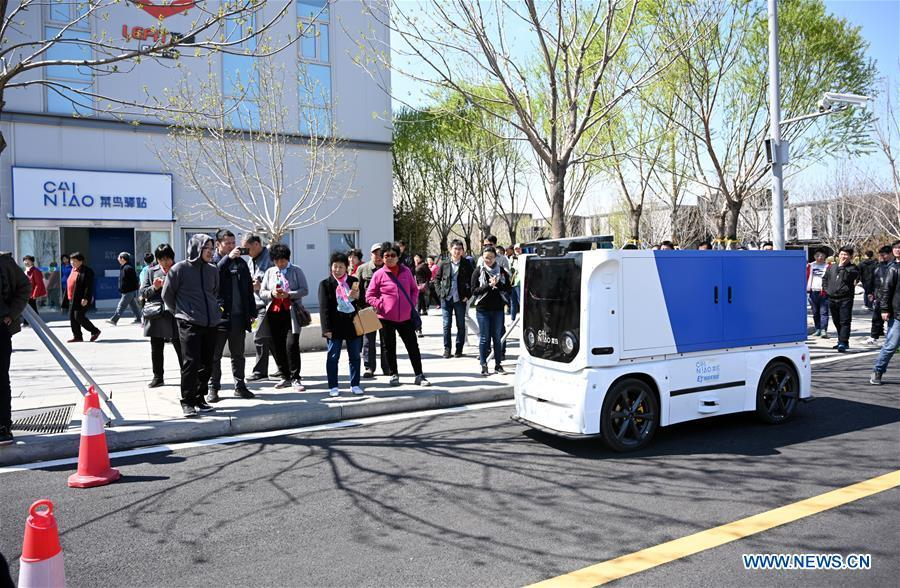 An unmanned express delivery vehicle runs on the street of Xiongan citizen service center in Xiongan New Area, north China\'s Hebei Province on March 31, 2019. The unmanned express delivery vehicle, independently researched and developed by Cainiao Network, Alibaba\'s logistics arm, was recently put into service at Xiongan citizen service center. The new energy vehicle can convey about 200 small packages at one time from delivery station to intelligent cabinet. (Xinhua/Jin Liangkuai)