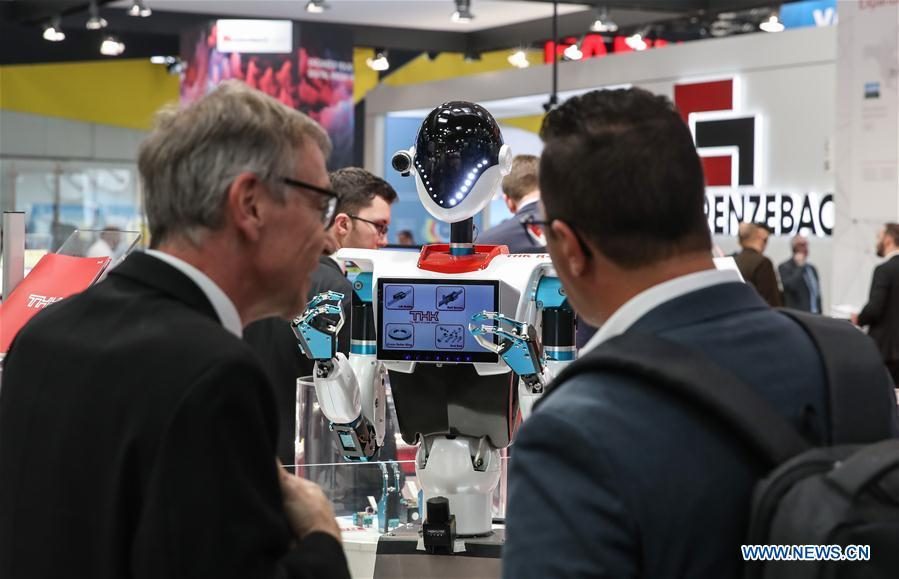 Visitors look at a robot displayed at the booth of THK during the 2019 Hanover Fair in Hanover, Germany, on April 1, 2019. With a total of 6,500 exhibitors from 75 countries and regions, the Hanover Fair shows the latest development of technologies for industrial use, including 5G network, artificial intelligence, light-weight manufacturing, among others. (Xinhua/Shan Yuqi)