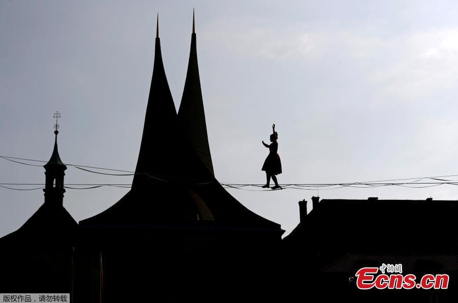 A tightrope?walker performs on ropes stretched over the Emmaus Monastery in Prague, Czech Republic, April 1, 2019. (Photo/Agencies)