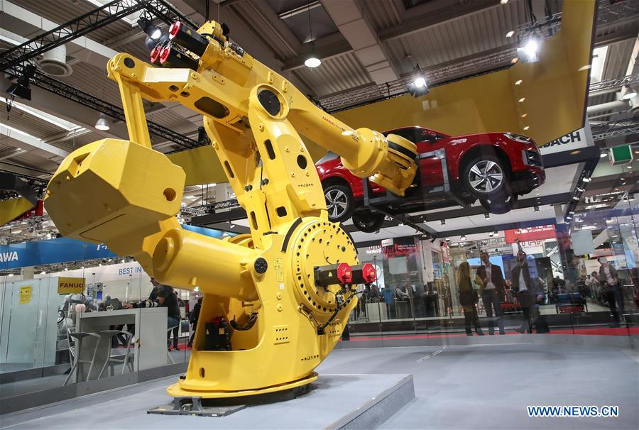 A robotic arm lifts a vehicle at the booth of FANUC during the 2019 Hanover Fair in Hanover, Germany, on April 1, 2019. With a total of 6,500 exhibitors from 75 countries and regions, the Hanover Fair shows the latest development of technologies for industrial use, including 5G network, artificial intelligence, light-weight manufacturing among others. (Xinhua/Shan Yuqi)
