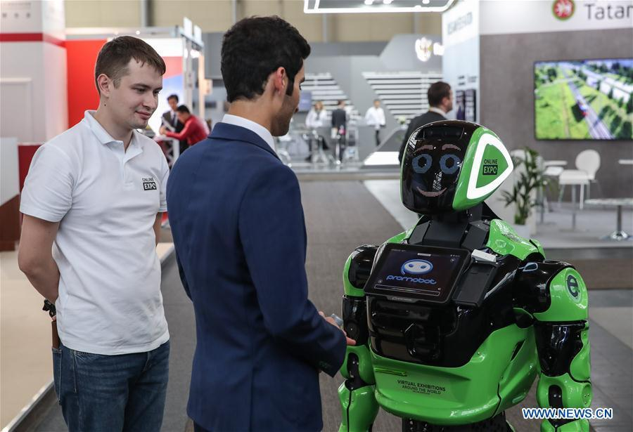 A visitor interacts with a robot at the booth of Russia during the 2019 Hanover Fair in Hanover, Germany, on April 1, 2019. With a total of 6,500 exhibitors from 75 countries and regions, the Hanover Fair shows the latest development of technologies for industrial use, including 5G network, artificial intelligence, light-weight manufacturing, among others. (Xinhua/Shan Yuqi)