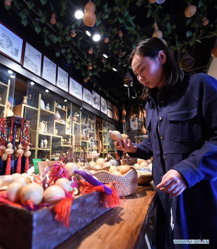 Ruan Xiyue, the fourth generation artist of Carved Gourd Ruan, arranges the handicrafts at a gourd carving studio in Lanzhou, northwest China\'s Gansu Province, April 1, 2019. A carved gourd, as the name suggests, is a gourd carved with landscapes, portraits, animals, calligraphy or poems, and then painted with ink. The process of gourd carving includes choosing gourd, painting, engraving and coloring. It was inscribed in the first group of provincial intangible cultural heritages of Gansu in 2006. (Xinhua/Fan Peishen)
