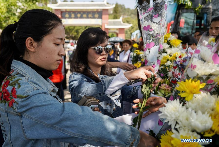 People present bouquets during a spontaneous mourning ceremony to pay tribute to those who lost their lives while fighting the forest fire in a funeral parlour in Xichang City, southwest China\'s Sichuan Province, April 2, 2019. A fire that killed 30 people and engulfed about 15 hectares of forest in southwest China\'s Sichuan Province was extinguished Tuesday, local authorities said. Thirty people, including 27 firefighters and three locals, lost their lives while fighting the fire. (Xinhua/Zhang Chaoqun)