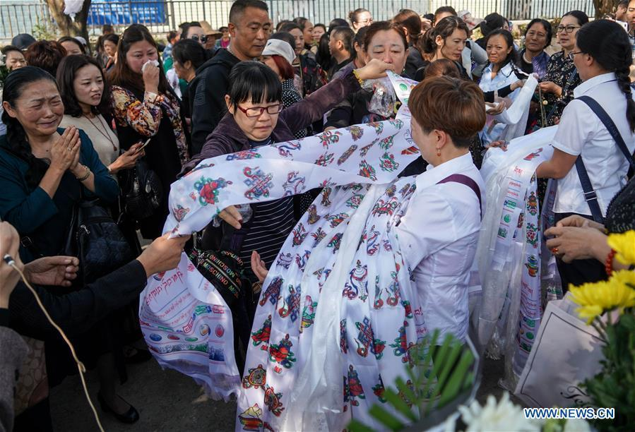 People present hada, a ceremonial silk cloth to show respect, during a spontaneous mourning ceremony to pay tribute to those who lost their lives while fighting the forest fire in a funeral parlour in Xichang City, southwest China\'s Sichuan Province, April 2, 2019. A fire that killed 30 people and engulfed about 15 hectares of forest in southwest China\'s Sichuan Province was extinguished Tuesday, local authorities said. Thirty people, including 27 firefighters and three locals, lost their lives while fighting the fire. (Xinhua/Zhang Chaoqun)