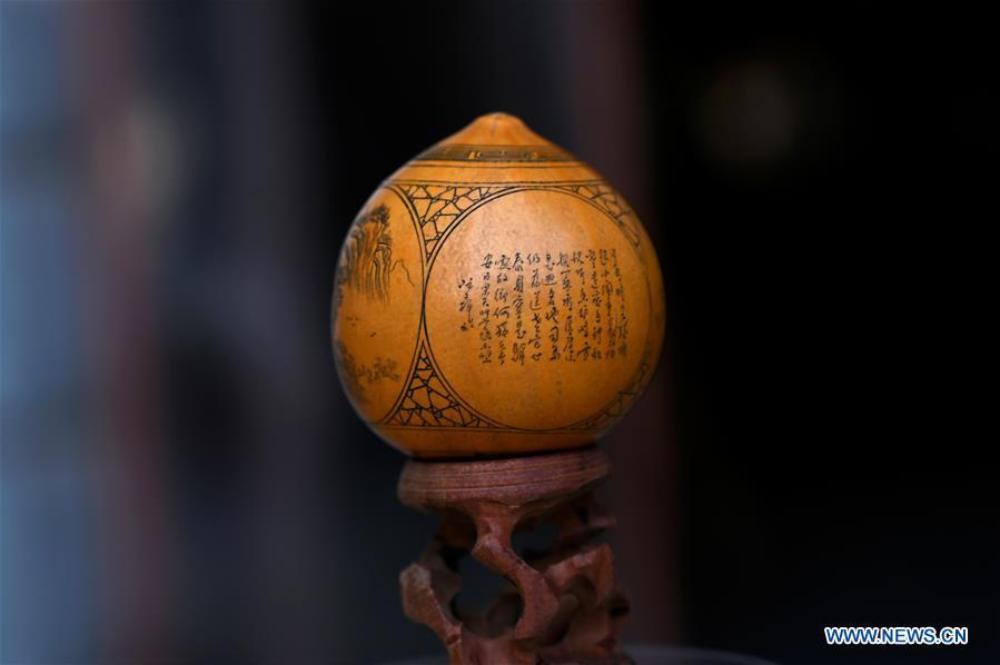 Photo taken on March 31, 2019 shows a carved gourd, created by Ruan Wenhui, a master of Chinese arts and crafts, at a gourd carving studio in Lanzhou, northwest China\'s Gansu Province. A carved gourd, as the name suggests, is a gourd carved with landscapes, portraits, animals, calligraphy or poems, and then painted with ink. The process of gourd carving includes choosing gourd, painting, engraving and coloring. It was insciribed in the first group of provincial intangible cultural heritages of Gansu in 2006. (Xinhua/Liu Jie)