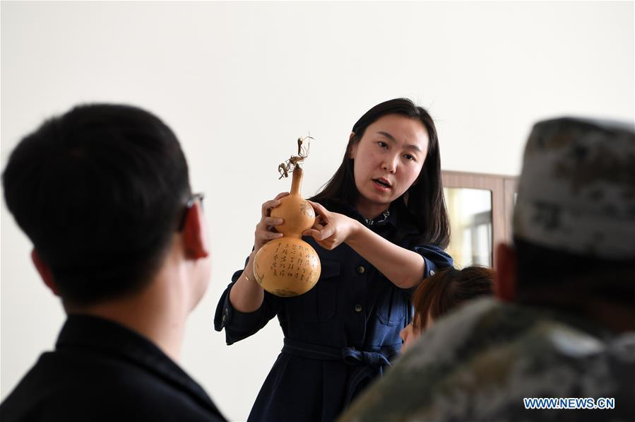 Ruan Xiyue, the fourth generation artist of Carved Gourd Ruan, teaches her students at Lanzhou Vocational Technical College in Lanzhou, northwest China\'s Gansu Province, April 1, 2019. A carved gourd, as the name suggests, is a gourd carved with landscapes, portraits, animals, calligraphy or poems, and then painted with ink. The process of gourd carving includes choosing gourd, painting, engraving and coloring. It was inscribed in the first group of provincial intangible cultural heritages of Gansu in 2006. (Xinhua/Fan Peishen)