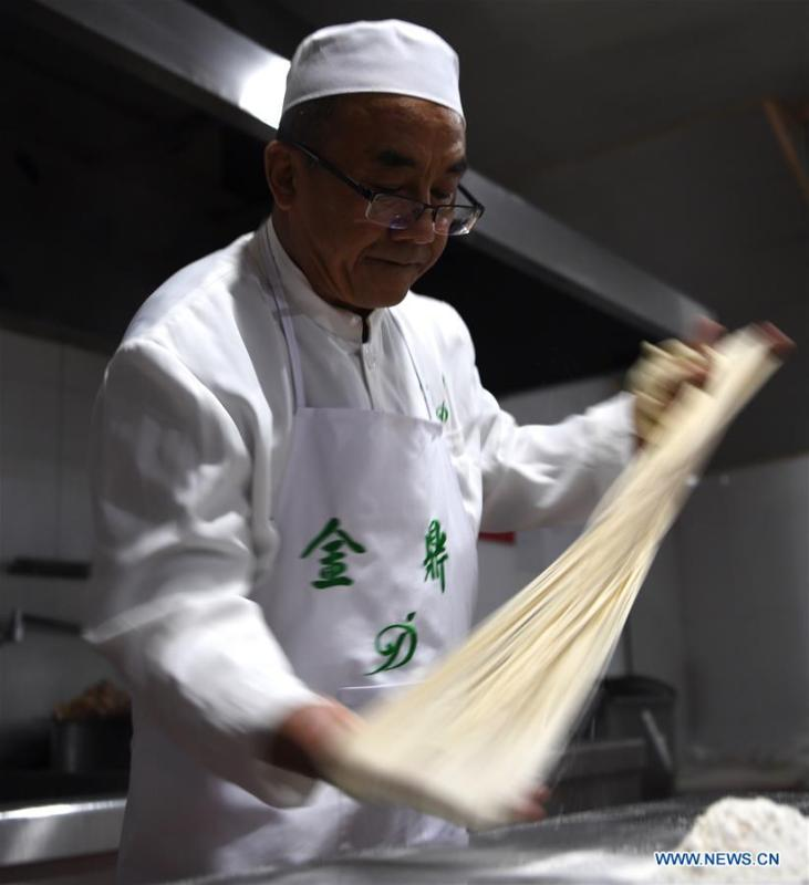 Ma Wenbin, an inheritor of Lanzhou beef noodle, pulls noodles at a beef noodle restaurant in Lanzhou, capital of northwest China\'s Gansu Province, April 2, 2019. Lanzhou beef noodles, a Chinese hand-pulled noodle originated in Lanzhou, has a history of about 100 years. There are about ten types of noodles of different width and shapes, depending on noodle chefs\' pulling skills. It has won fame both at home and abroad with its speciality of noodles and soup recipe. (Xinhua/Fan Peishen)