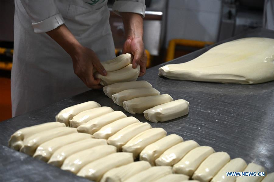 A noodle chef arranges the doughs to be pulled at a beef noodle restaurant in Lanzhou, capital of northwest China\'s Gansu Province, April 2, 2019. Lanzhou beef noodles, a Chinese hand-pulled noodle originated in Lanzhou, has a history of about 100 years. There are about ten types of noodles of different width and shapes, depending on noodle chefs\' pulling skills. It has won fame both at home and abroad with its speciality of noodles and soup recipe. (Xinhua/Liu Jie)
