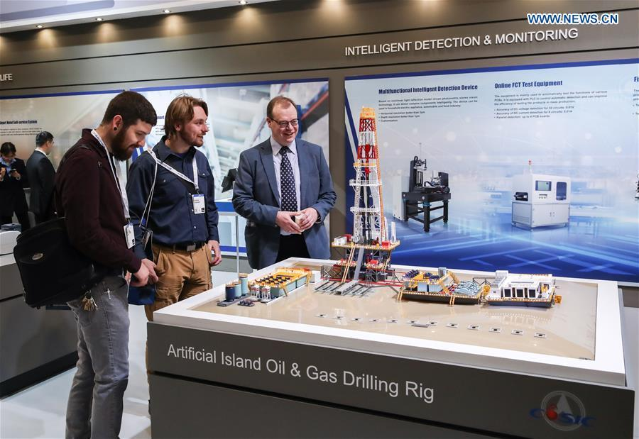 Visitors view a model of artificial island oil and gas drilling rig displayed at the booth of China Aerospace Science and Industry Corporation (CASIC) at Hanover Fair 2019 in Hanover, Germany, April 2, 2019. Over 1,400 Chinese exhibitors attended the fair, the second most just after the host country Germany. Huawei, Haier and other Chinese manufacturers showed their most advanced networking and artificial intelligence technologies to the world. (Xinhua/Shan Yuqi)