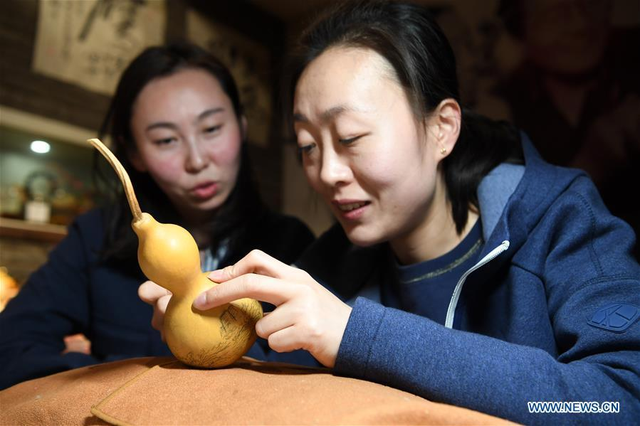 Ruan Xiyue (L), the fourth generation artist of Carved Gourd Ruan, communicates with Ruan Yizhou, an arts and crafts master of Gansu Province, at a gourd carving studio in Lanzhou, northwest China\'s Gansu Province, April 1, 2019. A carved gourd, as the name suggests, is a gourd carved with landscapes, portraits, animals, calligraphy or poems, and then painted with ink. The process of gourd carving includes choosing gourd, painting, engraving and coloring. It was inscribed in the first group of provincial intangible cultural heritages of Gansu in 2006. (Xinhua/Fan Peishen)