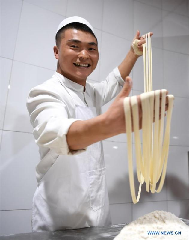 A noodle chef pulls noodles at a beef noodle restaurant in Lanzhou, capital of northwest China\'s Gansu Province, April 2, 2019. Lanzhou beef noodles, a Chinese hand-pulled noodle originated in Lanzhou, has a history of about 100 years. There are about ten types of noodles of different width and shapes, depending on noodle chefs\' pulling skills. It has won fame both at home and abroad with its speciality of noodles and soup recipe. (Xinhua/Fan Peishen)