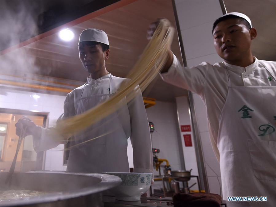 Noodle chefs boil noodles at a beef noodle restaurant in Lanzhou, capital of northwest China\'s Gansu Province, April 2, 2019. Lanzhou beef noodles, a Chinese hand-pulled noodle originated in Lanzhou, has a history of about 100 years. There are about ten types of noodles of different width and shapes, depending on noodle chefs\' pulling skills. It has won fame both at home and abroad with its speciality of noodles and soup recipe. (Xinhua/Fan Peishen)
