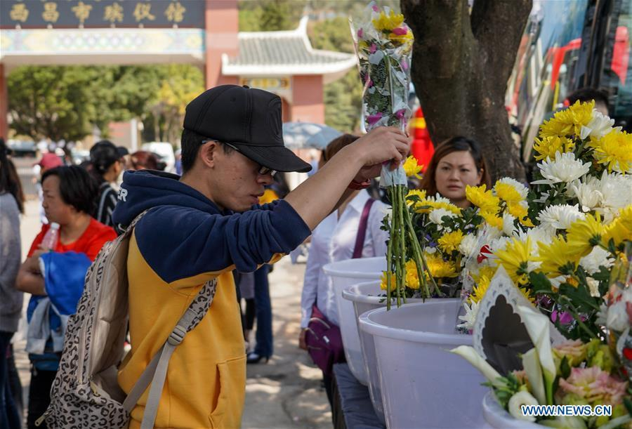 A citizen presents a bouquet during a spontaneous mourning ceremony to pay tribute to those who lost their lives while fighting the forest fire in a funeral parlour in Xichang City, southwest China\'s Sichuan Province, April 2, 2019. A fire that killed 30 people and engulfed about 15 hectares of forest in southwest China\'s Sichuan Province was extinguished Tuesday, local authorities said. Thirty people, including 27 firefighters and three locals, lost their lives while fighting the fire. (Xinhua/Zhang Chaoqun)
