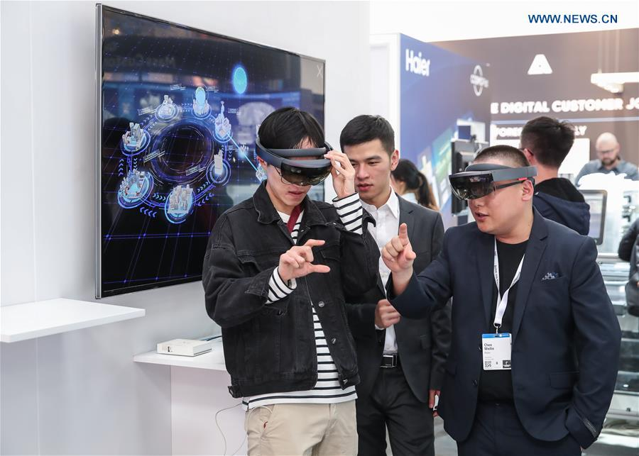 A visitor tries MR (Mixed reality) devices at the booth of China\'s consumer electronics and home appliances company Haier at Hanover Fair 2019 in Hanover, Germany, April 1, 2019. Over 1,400 Chinese exhibitors attended the fair, the second most just after the host country Germany. Huawei, Haier and other Chinese manufacturers showed their most advanced networking and artificial intelligence technologies to the world. (Xinhua/Shan Yuqi)