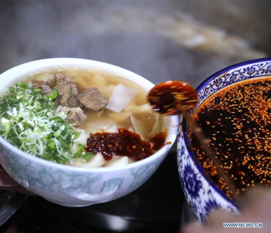 A noodle chef adds chili oil to noodles at a beef noodle restaurant in Lanzhou, capital of northwest China\'s Gansu Province, April 2, 2019. Lanzhou beef noodles, a Chinese hand-pulled noodle originated in Lanzhou, has a history of about 100 years. There are about ten types of noodles of different width and shapes, depending on noodle chefs\' pulling skills. It has won fame both at home and abroad with its speciality of noodles and soup recipe. (Xinhua/Li Xiao)