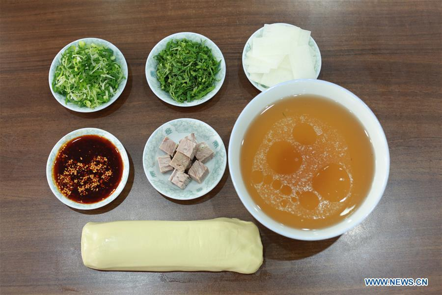 Photo taken on April 2, 2019 shows materials and seasoners for making Lanzhou beef noodles at a noodle restaurant in Lanzhou, capital of northwest China\'s Gansu Province. Lanzhou beef noodles, a Chinese hand-pulled noodle originated in Lanzhou, has a history of about 100 years. There are about ten types of noodles of different width and shapes, depending on noodle chefs\' pulling skills. It has won fame both at home and abroad with its speciality of noodles and soup recipe. (Xinhua/Ma Ping)