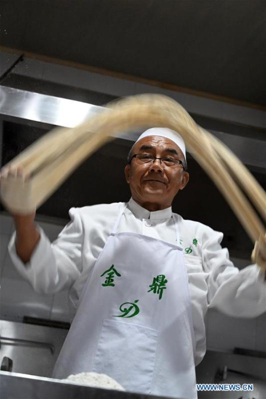 Ma Wenbin, an inheritor of Lanzhou beef noodles, pulls noodles at a beef noodle restaurant in Lanzhou, capital of northwest China\'s Gansu Province, April 2, 2019. Lanzhou beef noodles, a Chinese hand-pulled noodle originated in Lanzhou, has a history of about 100 years. There are about ten types of noodles of different width and shapes, depending on noodle chefs\' pulling skills. It has won fame both at home and abroad with its speciality of noodles and soup recipe. (Xinhua/Liu Jie)