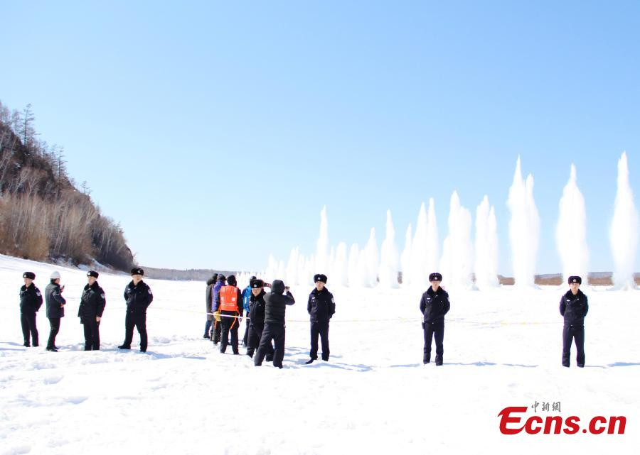 Police officers stand guard as ice is blasted to create safe passage for ships on the still-frozen Tahe section of Heilongjiang River in Northeast China\'s Heilongjiang Province, April 3, 2019. As the weather starts to warm after the extreme cold of winter, local authorities detonate the thick ice to allow vessels to start work again.  (Photo/China News Service)