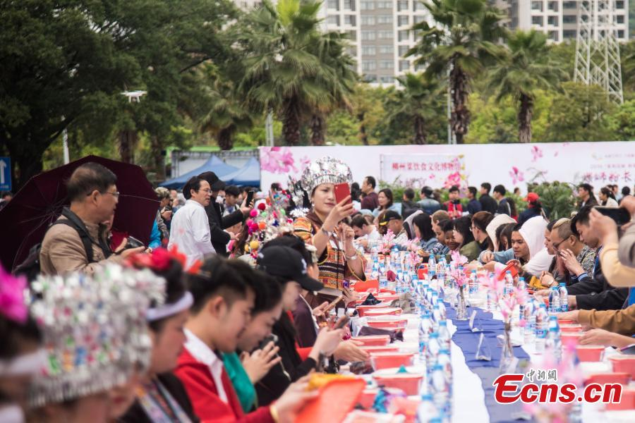 People eat Luosifen, a local rice noodle dish featuring cooked river snails as ingredient, at a long-table feast in Liuzhou, south China\'s Guangxi Zhuang Autonomous Region, April 3, 2019. More than 2,000 people joined the feast which was served on tables measuring 1,000 meters in length here on Wednesday.  (Photo/China News Service)