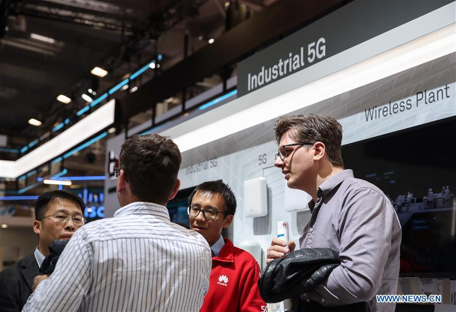 A staff member (L) introduces a Huawei product as a visitor looks on at the booth of Huawei during the 2019 Hanover Fair in Hanover, Germany, April 3, 2019. (Xinhua/Shan Yuqi)