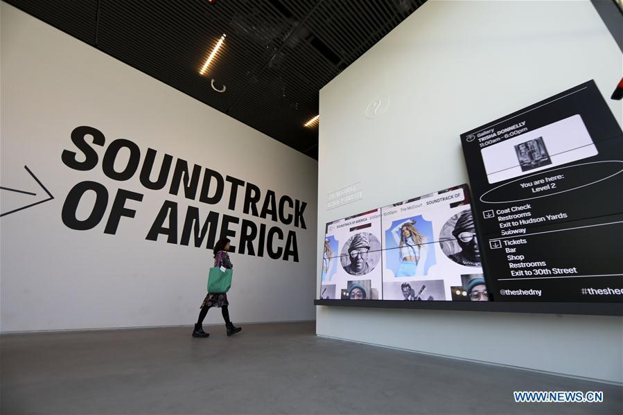 A visitor walks past screens during a media preview in The Shed, a new arts center in New York, the United States, on April 3, 2019. The Shed, New York City\'s new arts center that commissions, develops, and presents original works of art, across all disciplines, for all audiences, will open to the public on April 5 with the world premiere of Soundtrack of America. (Xinhua/Wang Ying)