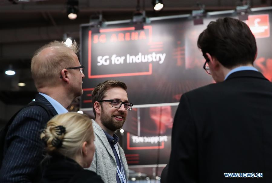 Visitors talk with a staff member at the 5G Arena during the 2019 Hanover Fair in Hanover, Germany, April 1, 2019. (Xinhua/Shan Yuqi)