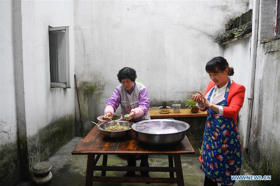 Villagers make Qingtuan, or green sticky rice balls, in Yiyanshan Village of Huzhou, east China\'s Zhejiang Province, April 4, 2019. Qingtuan, made from glutinous rice mixed with wormwood juice and stuffed with bamboo shoot, tofu and preserved meat, is a traditional snack popular mailnly among people living in the south of Yangtze River during the Qingming Festival also known as Tomb Sweeping Day. (Xinhua/Huang Zongzhi)