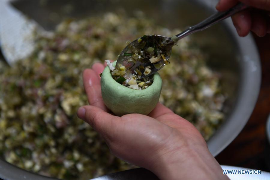 A villager makes Qingtuan, or green sticky rice balls, in Yiyanshan Village of Huzhou, east China\'s Zhejiang Province, April 4, 2019. Qingtuan, made from glutinous rice mixed with wormwood juice and stuffed with bamboo shoot, tofu and preserved meat, is a traditional snack popular mailnly among people living in the south of Yangtze River during the Qingming Festival also known as Tomb Sweeping Day. (Xinhua/Huang Zongzhi)