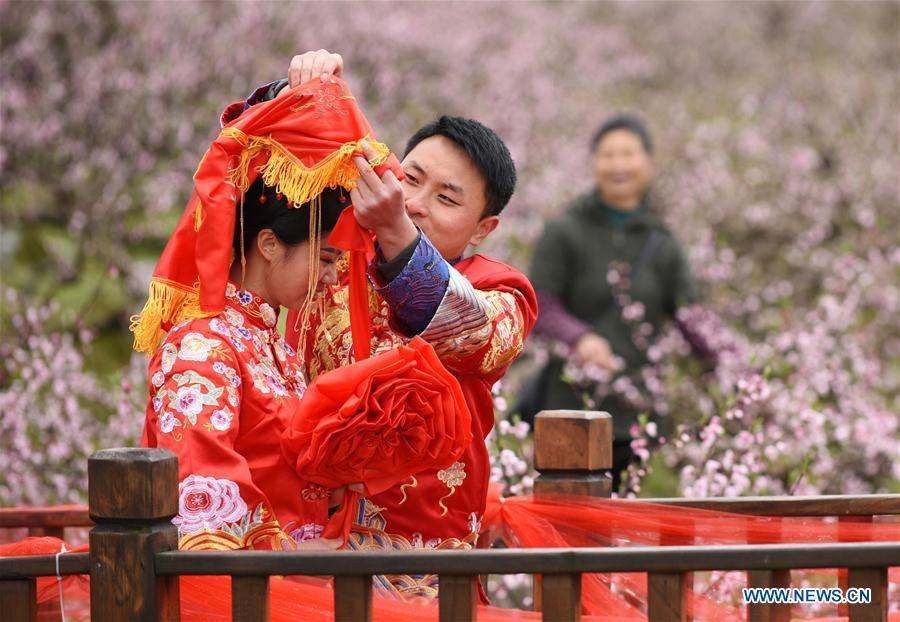 A groom arranges red bridal veil for his bride during a group wedding ceremony in traditional style in Wude Town of Shiqian County, southwest China\'s Guizhou Province, April 4, 2019. A group wedding ceremony in traditional style was held here Thursday for couples who have been striving on the frontline for the county\'s fight against poverty. (Xinhua/Yang Wenbin)