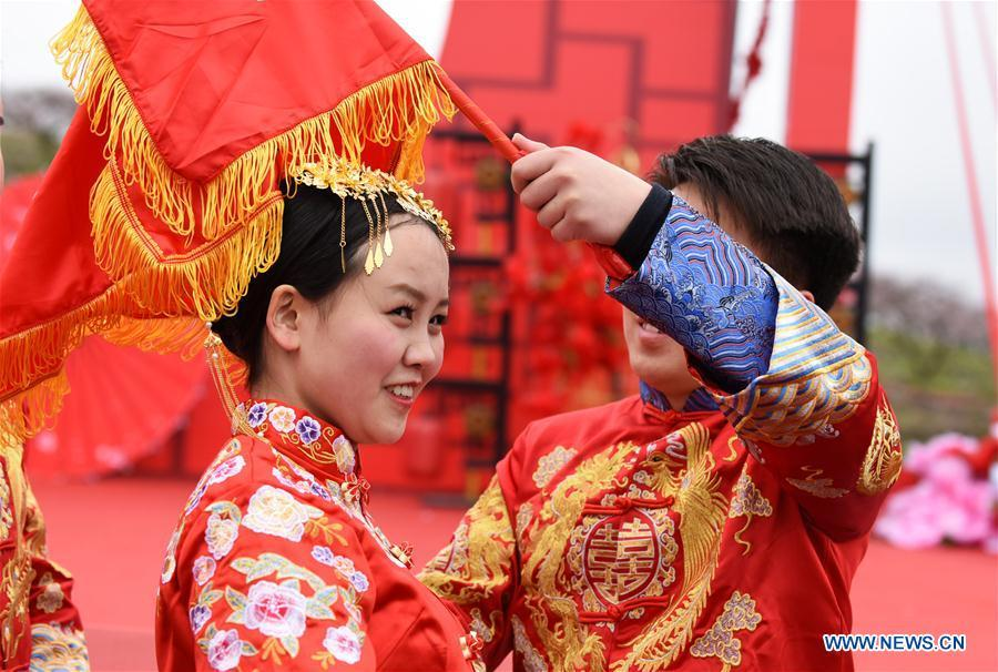 A groom lifts red bridal veil for his bride during a group wedding ceremony in traditional style in Wude Town of Shiqian County, southwest China\'s Guizhou Province, April 4, 2019. A group wedding ceremony in traditional style was held here Thursday for couples who have been striving on the frontline for the county\'s fight against poverty. (Xinhua/Yang Wenbin)