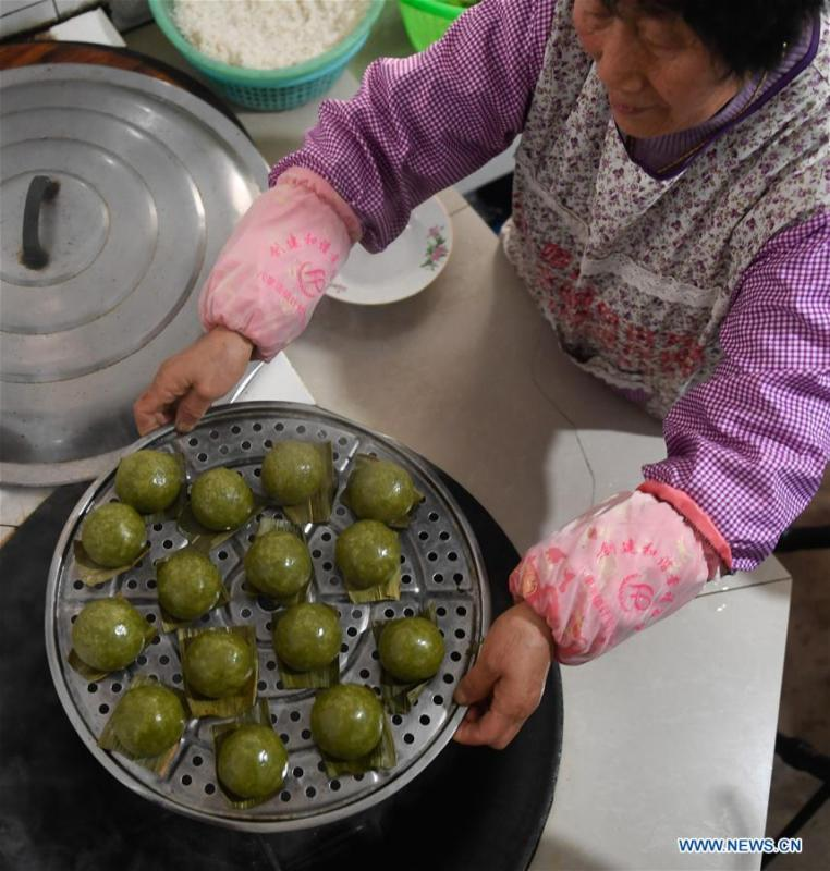 A villager shows steamed Qingtuan, or green sticky rice balls, in Yiyanshan Village of Huzhou, east China\'s Zhejiang Province, April 4, 2019. Qingtuan, made from glutinous rice mixed with wormwood juice and stuffed with bamboo shoot, tofu and preserved meat, is a traditional snack popular mailnly among people living in the south of Yangtze River during the Qingming Festival also known as Tomb Sweeping Day. (Xinhua/Huang Zongzhi)