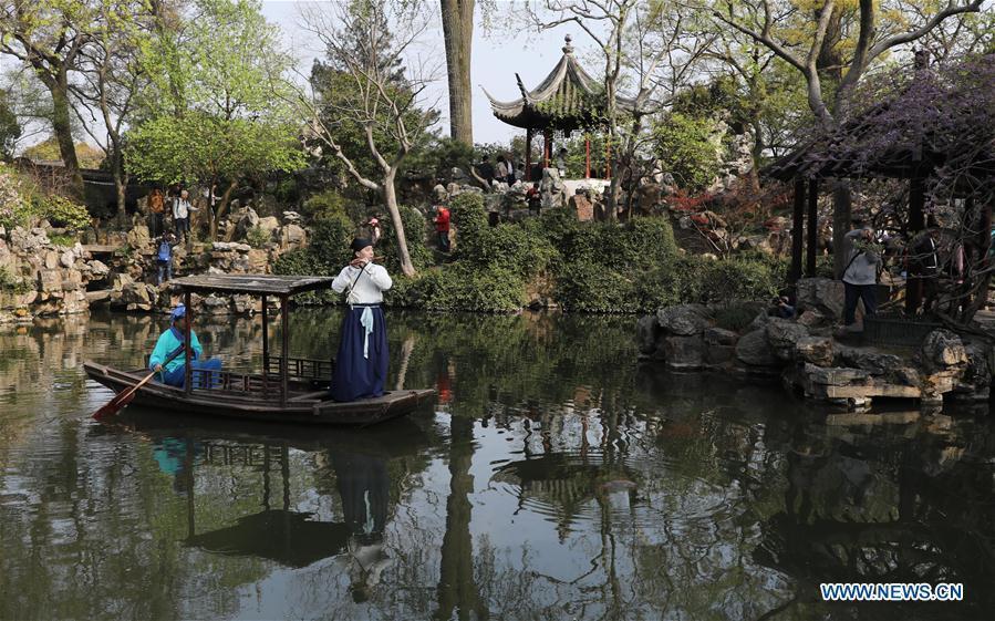 Tourists view an artist\'s performance in the Liuyuan garden during the Qingming Festival holidays in Suzhou, east China\'s Jiangsu Province, April 5, 2019. (Xinhua/Hang Xingwei)
