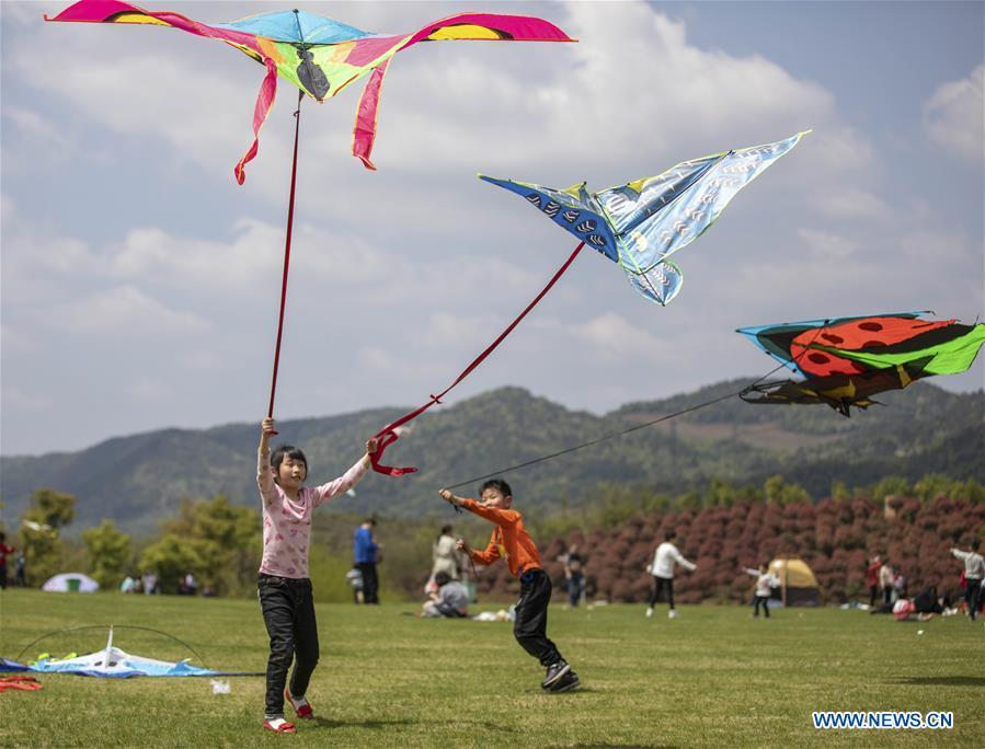 Children fly kites during the holiday for the Qingming Festival at Xiannyuhu scenic spot in Xinyu, east China\'s Jiangxi Province, April 5, 2019, (Xinhua/Zhao Chunliang)