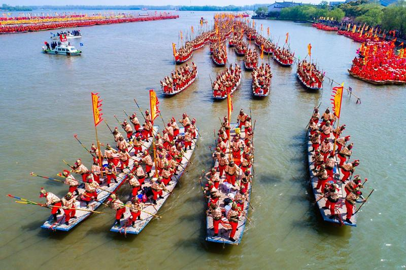 In this aerial photo taken on April 6, 2019, people get ready for a boat performance during the 2019 Qintong Boat Festival held at Qinhu National Wetland Park in Jiangyan District of Taizhou, East China\'s Jiangsu province. Hundreds of boats with more than 10,000 boat team members aboard gathered here on Saturday for the Qintong Boat Festival, which has been a centuries-old tradition.