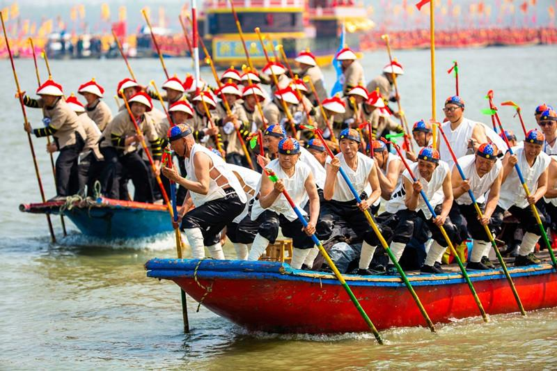 People participate in a boat performance during the 2019 Qintong Boat Festival held at Qinhu National Wetland Park in Jiangyan District of Taizhou, East China\'s Jiangsu province, April 6, 2019. Hundreds of boats with more than 10,000 boat team members aboard gathered here on Saturday for the Qintong Boat Festival, which has been a centuries-old tradition.