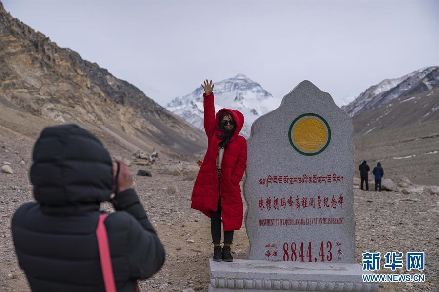 A tourist poses for a photo at the foot of the Mount Qomolangma in Southwest China's Tibet Autonomous Region, April 6, 2019.(Photo/Xinhua)